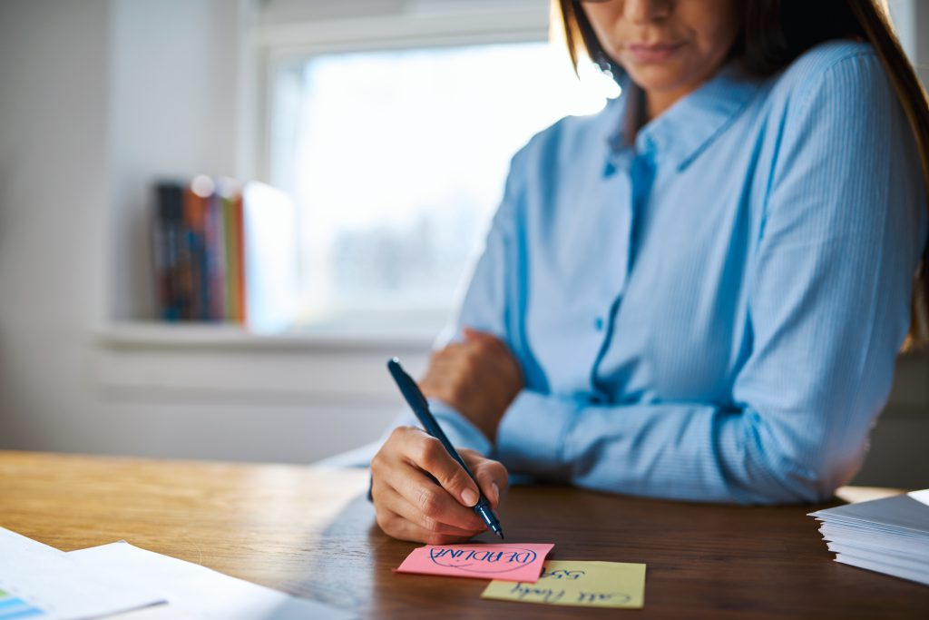 Person writing on sticky notes